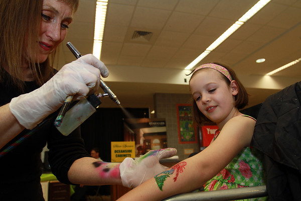 Michaela Bartlett,8, of Danvers, gets an airbrush tattoo from Marblehead artist Gayle Rosen of Flying Colors Face and Body Art at the Marblehead Home and Garden Show at Marblehead High School. David Le/Staff Photo