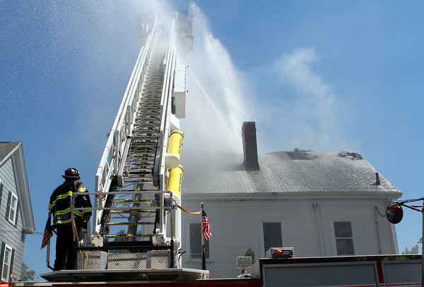 Peabody Firefighter Gene Clements stands guard at the base of Peabody Ladder 1 as it sprays water through the roof of 20 Endicott St. in Peabody on Wednesday afternoon. David Le/Staff Photo