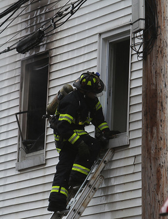 Peabody: A firefighter removes a second story window from 5 Hancock St. in Peabody after the blaze was extinguished. David Le/Salem News