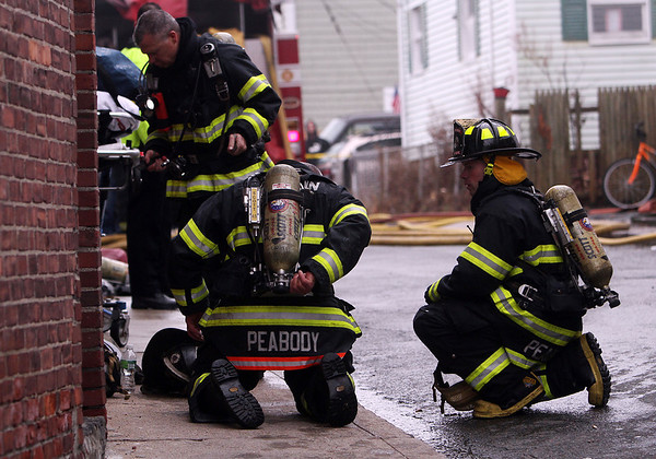 Peabody: A few Peabody firefighters take a break after fighting a 3-alarm fire on Hancock St. in Peabody on Friday afternoon. David Le/Salem News