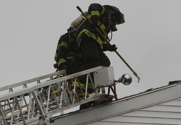 Peabody: Two Peabody firefighters use a sharp tool to poke a hole in the roof of 5 Hancock St. as they attempt to extinuguish the blaze on Friday afternoon., David Le/Salem News