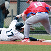 Danvers leadoff hitter AJ Couto manages to keep his fingers on third base as Burlington third baseman Chris Sharpe applies the tag. David Le/Staff Photo