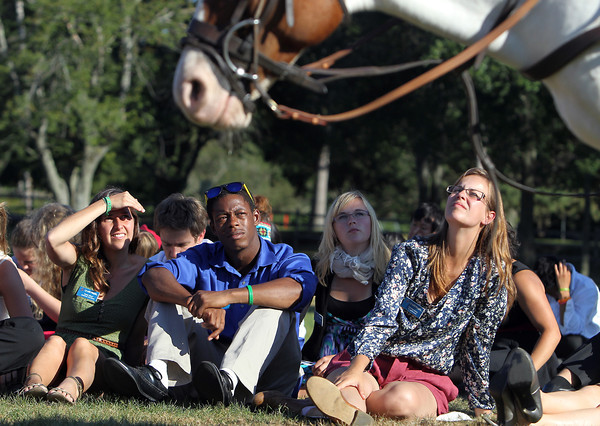 Up With People participants from left, Sanne Meert, Clyde Foxhall, and Yolanda Ketel, listen to Cissie Snow, a polo jockey from Myopia Polo Club, while visiting Patton Park on Monday afternoon. David Le/Staff Photo