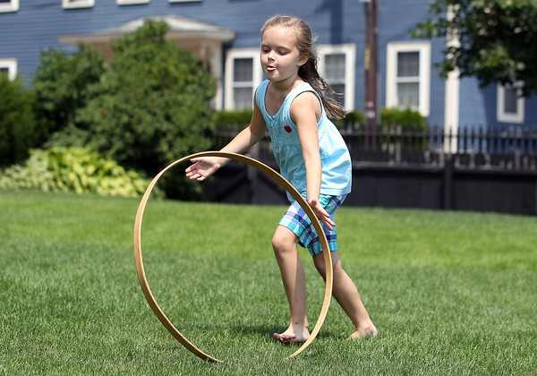 Elizabeth Swanson, 6, of Salem rolls a hoop across the lawn at the House of 7 Gables on Thursday afternoon while playing colonial games. David Le/Staff Photo