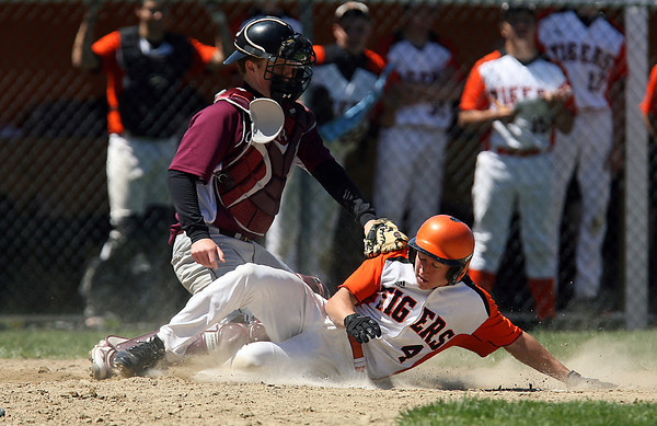 Ipswich senior Dan O'Flynn gets tagged out at the plate by Rockport catcher Caleb Tanson on a close play at the plate on Saturday morning. David Le/Staff Photo