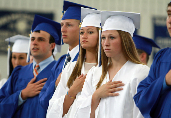 Swampscott High School graduates hold their hands over their hearts during the singing of the National Anthem on Sunday. David Le/Staff Photo