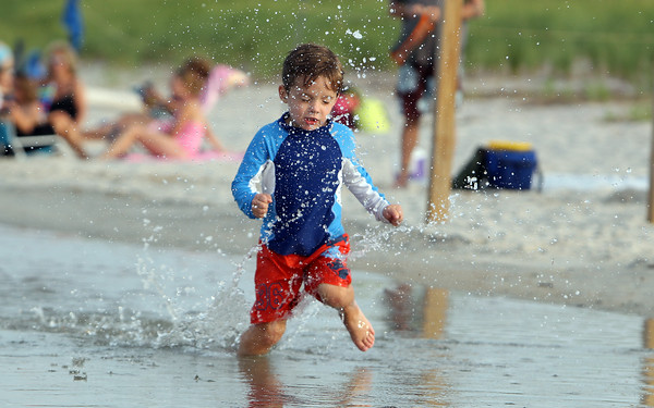 Nate Jackson, 3 1/2, of Danvers, splashes through the water at Crane's Beach in Ipswich on Friday evening. David Le/Staff Photo