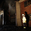 Danvers Fire Chief Kevin Farrell surveys some of the damage to the back of an apartment complex located on Folley Pond Road on Wednesday night. David Le/Salem News