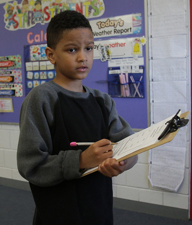 Robert Nash, a 2nd grader at Bentley Elementary School in Salem, compares his answers against answers written on a whiteboard on Tuesday afternoon. David Le/Salem News