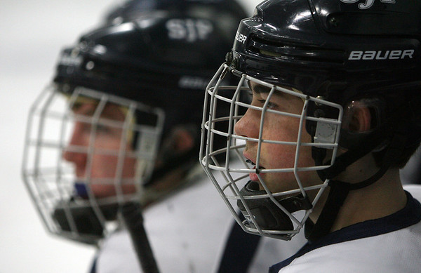 St. John's Prep __________ and his teammates intently follow the action on ice. David Le/Staff Photo