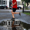Will Reardon, of Salem, runs past a puddle around the outskirts of Salem Common on Wednesday evening after a heavy rain all day. David Le/Staff Photo