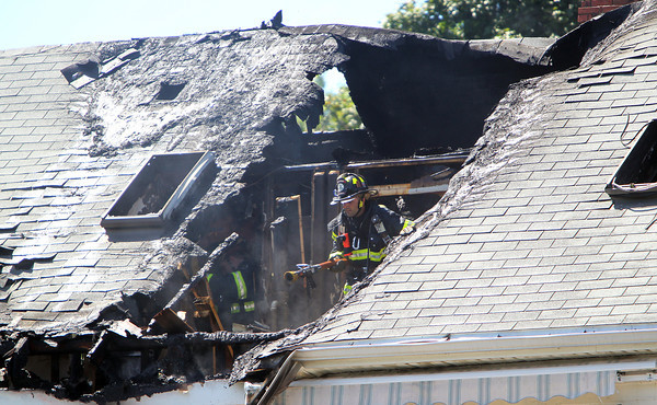 A Peabody firefighter drags a hose through a gaping hole in the roof of 20 Endicott St. in Peabody, after the main blaze was extinguished on Wednesday afternoon. David Le/Staff Photo