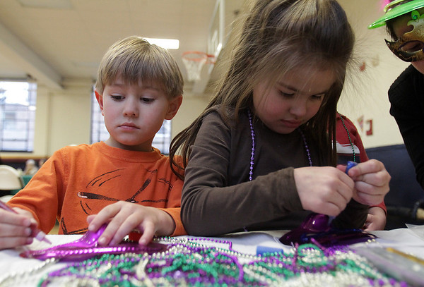 DJ Corbett, 4, and his sister Ellie, 6, of Beverly work on making Mardi Gras masks at St. Thomas the Apostle Church on Tuesday afternoon. David Le/Staff Photo