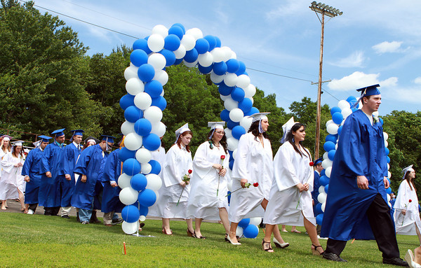 Danvers High School graduates march through arcs of blue and white balloons and into their Commencement Ceremony on Saturday afternoon. David Le/Staff Photo