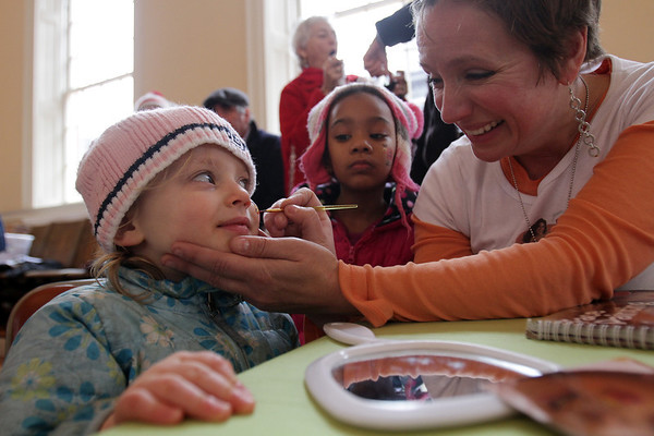 Nancy Lee Reed, 3, of Salem, left, gets her face painted by Brett Mentuck, of Salem, right, while Nancy's best friend Annah Malima, 5, also of Salem, looks on. David Le/Salem News
