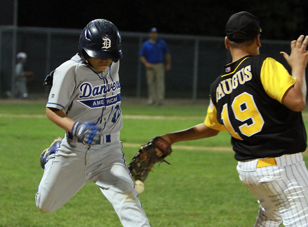 Danvers American runner Thomas Mento beats out a close play at first base as the ball caroms off the mitt of Saugus American's Gennaro Cardoso.