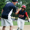 Danvers: The Peabody West thirdbase coach high-fives Cam Curley after the centerfielder hit a home run in the third inning of the Jimmy Fund Championship Game between Peabody West and Danvers American. After a hard-fought slugfest between the two teams, Danver American came out on top just barely holding onto an 8-7 victory to take home the championship. Photo by David Le/Salem News