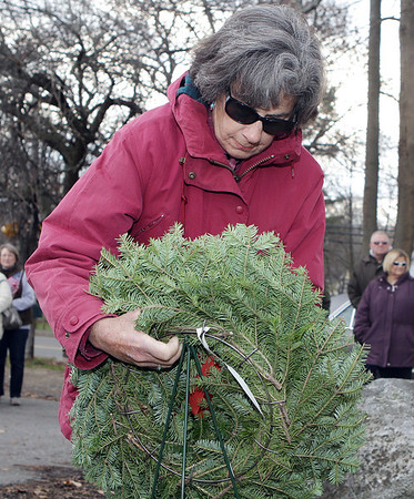Lois Bethune, places one of seven ceremonial wreaths at the Wreaths Across America ceremony held at St. Mary of the Annunciation Cemetary on Saturday afternoon in Danvers.David Le/Salem News