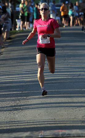 Meagan Nedlo, of Salem, sprints through shadows and towards the finish of the 45th Annual Beverly Homecoming Race at Lynch Park on Thursday evening. David Le/Staff Photo