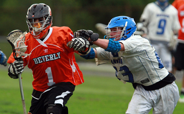 Beverly attack Ryan Shipp fends off a check from Danvers' Jay Calcagno, on Thursday evening. David Le/Staff Photo