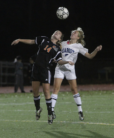 Peabody's Christa Trombley (9) right, battles for a header with Oliver Ames' Kristina Simonson on Tuesday night. David Le/Salem News