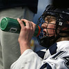 St. John's Prep sophmore Tyler Bird (14) grabs a squirt of water as he catches his breath on the bench. David Le/Staff Photo