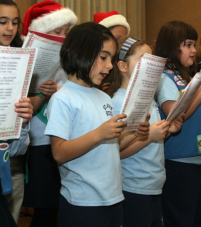 Peabody: Branae Craveiro, a Girl Scout from St. John the Baptist School, along with 35 other troop members sing Christmas carols for residents of Brooksby Village on Tuesday afternoon. David Le/Salem News