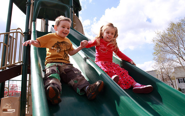 Siblings Nathan, 3, and Leela Sweetser, 4, of Beverly, hold hands as they zoom down a double slide at Kimball Haskell Park on Tuesday afternoon. David Le/Staff Photo