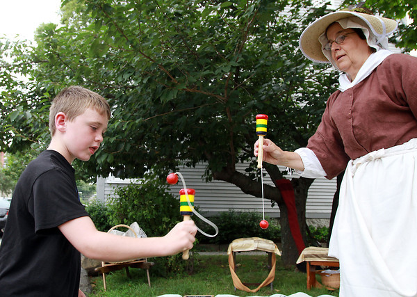 Jack Iles, 8, of Camillus, NY, tries to get the hang of a game at The Witch House in Salem with the help of re-enactor Donna Stavris, right. David Le/Staff Photo
