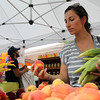 Rebecca Fuller, of Hamilton, picks out some peaches at the Salem Farmer's Market on Thursday afternoon. David Le/Staff Photo