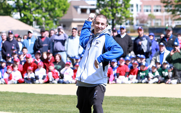 Danvers senior Jon Amico throws out one of the ceremonial first pitches at Danvers Americans' opening day festivities on Saturday morning. The Danvers High Basketball Team was honored for their State Championship by leading the parade through Danvers Square. David Le/Staff Photo