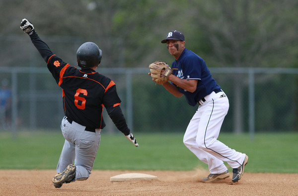 Danvers shortstop Nick Valles, right, looks to make a throw to first base around sliding Beverly baserunner Alex Toomey. David Le/Staff Photo