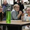 Buker Elementary School 5th graders Lily Ting, left, Nina Dooley, center, and Elizabeth Gasiorowski, right, laugh as they watch their podcasts being shown to school administration and committee members on Thursday night. David Le/Staff Photo.