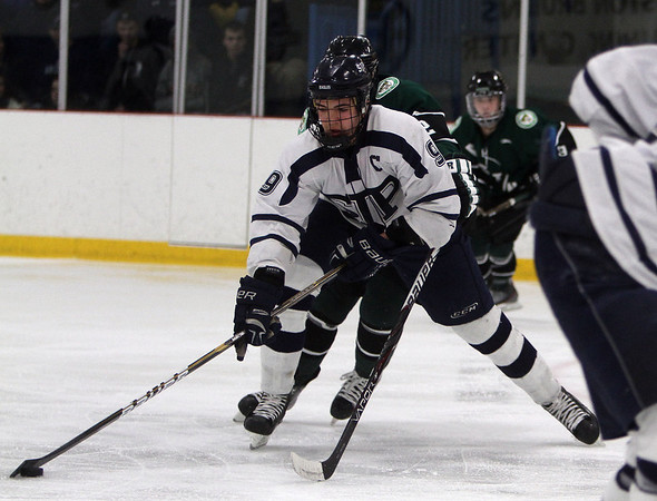 St. John's Prep captain Sam Kurker (9) controls the puck while being hassled by an Austin Prep defender. David Le/Staff Photo