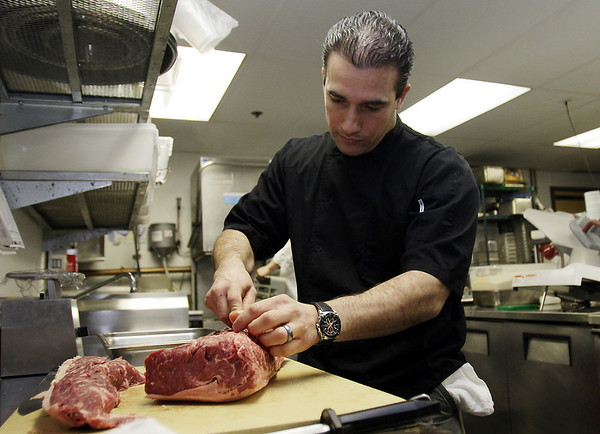 Head Chef and Owner of 62 Restaurant and Wine Bar, Tony Bettencourt, trims down and prepares portions of sirloin for dinner service. David Le/Salem News