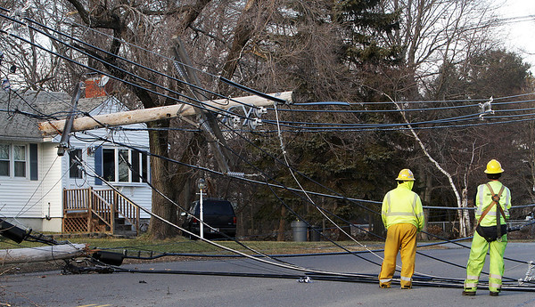 A couple Peabody Municipal Light workers wait for instructions to clear away wires and a suspended telephone pole from the middle of Herrick Road on Friday afternoon. David Le/Salem News