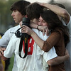 Masco junior Justin Clark (18) left, gets a hug from classmate Renee Ouellette, and a pat on the head from teammate Adam Grammer, right, after Clark drilled home the winning penalty kick on Wednesday to propel the Chieftans to the semi-finals of the MIAA State Tournament. David Le/Salem News