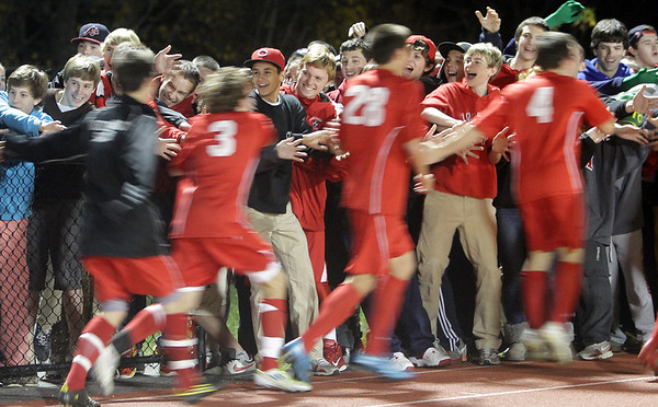 A large crowd of delighted Masco fans give high fives and congratulate the Chieftans on their 2-0 win over Greater New Bedford on Tuesday night in Weymouth. David Le/Salem News