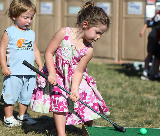 Danvers: Maggie Burridge, 4, of Georgetown tries to putt a mini golf ball while her brother Jake, 2 watches and waits for his turn. Photo by David Le/Salem News