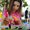 Ella Currier, 5, of Beverly, uses a sponge brush to cover a stamp with paint while making a colorful flag at the Beverly Homecoming Lobster Festival on Wednesday afternoon. David Le/Staff Photo