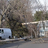 Tree branches and telephone and electrical wires littered Herrick Road on Friday afternoon after a truck stuck a telephone pole, snapping it in half. The top half of the pole can be seen suspended above the street. David Le/Salem News