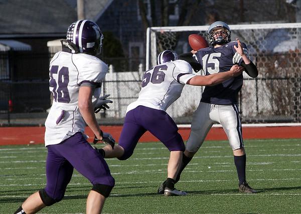 Hamilton-Wenham quarterback Steve Brao (15) gets rid of the ball as he gets hit by Bourne High School's Jack Schmitt. David Le/Salem News