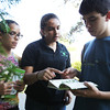Members of the All SET 4-H Club from left, Emily Fabre, 12, and Kaitlyn Fabre, 15, of Salem, and Nick Melanson, 15, of Peabody, pour over tree guides to identify a unique species of tree found in Greenlawn Cemetery in Salem. David Le/Staff Photo