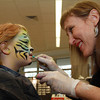 Emma Hood, 7, of Marblehead gets her face painted by local artist Gayle Rosen of Flying Colors Face and Body Art at Marblehead's Home and Garden Show. David Le/Staff Photo
