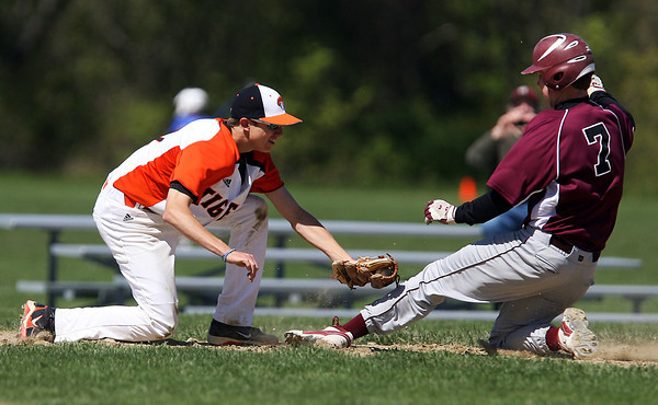 Ipswich High School third baseman Josh Guertin, left, tags out a Rockport runner on Saturday morning. David Le/Staff Photo