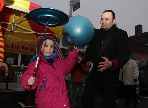 Beverly: Julia Crockett, 5, of Beverly, balances a plate on a stick and a bouncy ball on her finger with the help of Smyly the Juggler along Cabot St. on New Year's Eve. David Le/Salem News