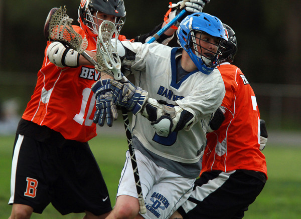Danvers attacker Will Jennings (9) center, tries to spin away from the defensive pressure of Beverly's Dave Rollins, left, and Andrew Irving, right, on Thursday evening. David Le/Staff Photo