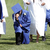 "Danvers High School senior Nick Valles ""Tebows"" before walking across the stage to receive his diploma on Saturday afternoon. David Le/Staff Photo"