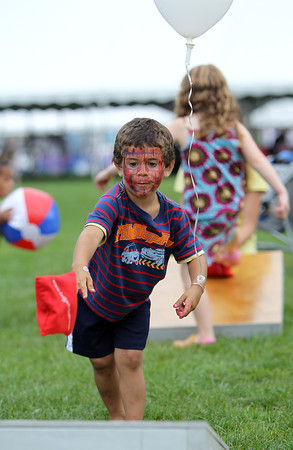 Jadel Salazar, 3, of Beverly plays cornhole at the Beverly Homecoming Lobster Festival on Wednesday afternoon at Lynch Park. David Le/Staff Photo