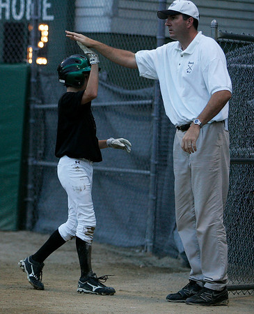 Beverly: Beverly West coach Dan Kozlowski high fives thirdbaseman Matt Townsend as he comes back to the dugout after scoring Beverly's first run of the night in the District 15 Little League Championship Game against Peabody West at Harry Ball field in Beverly. The game was postponed in the bottom of the 5th inning on Friday evening due to lightening and will resume Saturday afternoon at 5. Photo by David Le/Salem News
